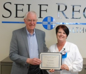 Self Regional's former CEO John Heydel presents Julie Culbertson with the M. John and Drenda Heydel Respiratory Therapy scholarship.
