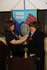 Lorraine Angelino of Greenwood is installed as the new Rotary District Governor during a special event held at Piedmont Technical College in June. Here, she receives a pin from Kim Gramling, the immediate past District Governor, who is from Seneca.
