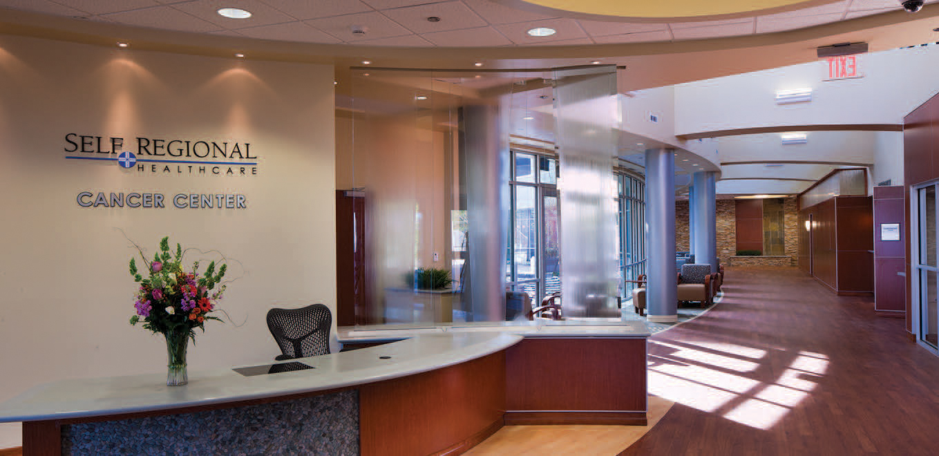 Sunlit garden hallway and welcome desk for Cancer Center at Self Regional Healthcare